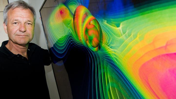 Der Physiker Karsten Danzmann, Direktor am Max-Planck-Institut für Gravitationsphysik, vor einer Visualisierung von Gravitationswellen.