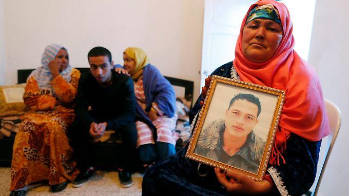 Die Mutter von Anis Amri (r.) und drei seiner Geschwister mit einem Bild des mutmaßlichen Attentäters von Berlin.