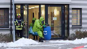 Im Justizzentrum Gera tragen die Feuerwehrleute Schutzanzüge.