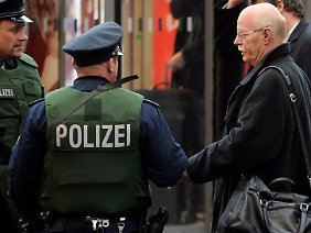 Ex-Verteidigungsminister Peter Struck (SPD) spricht vor dem Berliner Hauptbahnhof mit Polizisten.