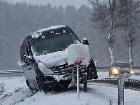 Von der Straße gerutscht: Dieser Kleintransporter kam bei Mengeringhausen in Hessen bei schneeglatten Straßen erst auf der Leitplanke zum Stehen.