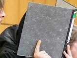 Die Angeklagten mit Aktenordnern vor dem Gesicht sollen an Filialen in Wattenscheid, Bottrop und Herten Bomben gezündet haben.