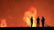 Bewohner von Pumanque starren zusammen mit Feuerwerleuten fassungslos in die Flammen.