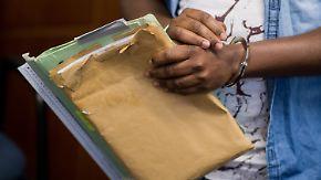 """Der Angeklagte Abakar O. steht am 06.02.2017 mit Handschellen im Amtsgericht in Hannover (Niedersachsen). Der Asylbewerber aus dem Sudan hat vor Gericht Sozialbetrug mit einem Schaden von 21 700 Euro zugegeben. Er habe mit dem Geld seine erkrankten Eltern in seiner Heimat unterstützen wollen und dazu bei den Behörden in mehreren Städten verschiedene Identitäten angegeben. (zu dpa """"Asylbewerber gibt Sozialbetrug zu"""" vom 06.02.2016) Foto: Julian Stratenschulte/dpa +++(c) dpa - Bildfunk+++"""