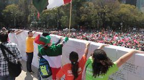 Demonstranten reißen eine falsche Mauer ein.