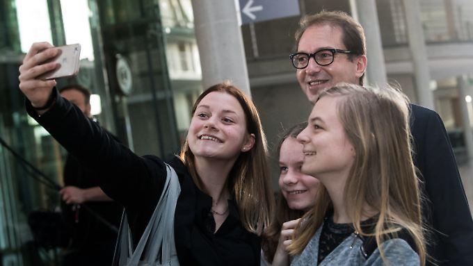 Volksnah: Verkehrsminister Dobrindt lässt junge Bundestagsbesucherinnen vor der Ausschusssitzung Selfies mit sich machen.