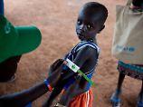 Ein Mitarbeiter von Unicef untersucht mithilfe eines Maßbandes am Unterarm des kleines Jungen, ob er an Unterernährung leidet. Tausende Kinder im Südsudan sind mangelernährt.