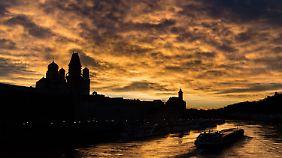 Ein Schiff fährt über die Donau in Passau, während im Hintergrund der Abendhimmel über den Silhouetten vom Passauer Dom St. Stephan, dem alten Rathaus und der Kirche St. Paul leuchtet.