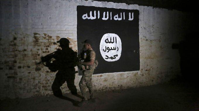 Ein irakischer Soldat untersucht in Mossul einen Zugtunnel mit einer Wandmalerei der IS-Flagge. Er soll von IS-Kämpfern als Trainingscamp genutzt worden sein.