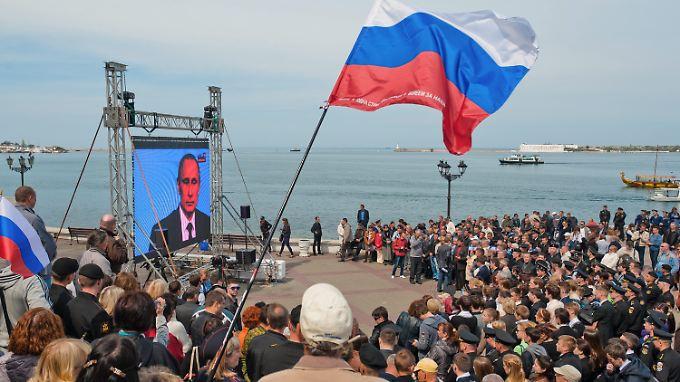 Menschen in Sewastopol auf der Krim sehen sich eine Fernseh-Ansprache des russischen Präsidenten an (Archivbild von 2014).