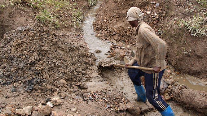 Ein junger Arbeitet sucht in einer Mine in der ostkongolesischen Provinz nach Rückständen des wertvollen Zinnerzes Kassiterit,