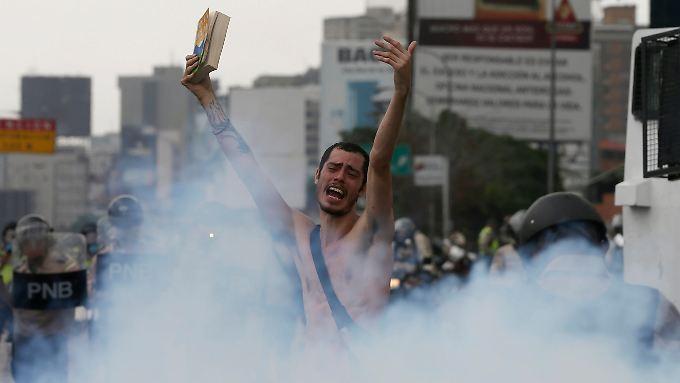 Ein Demonstrant in Caracas: Nackt richtete er seinen Appell an die Polizei, die ihn in Tränengas einhüllt.