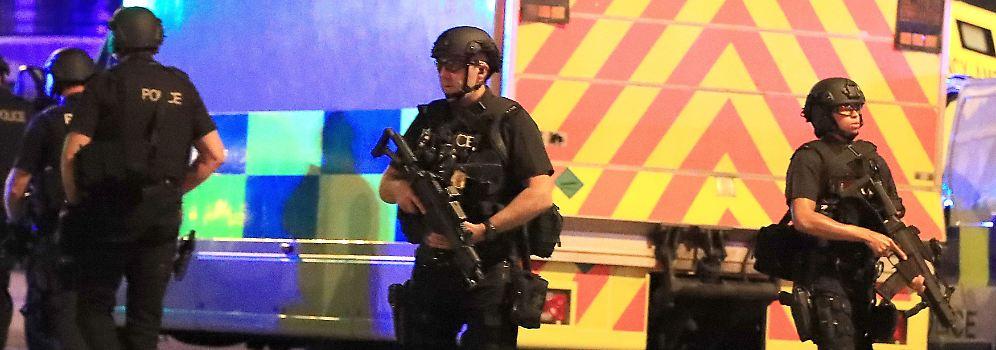 Schwerbewaffnete Polizisten sichern das Gebiet rund um die Halle.