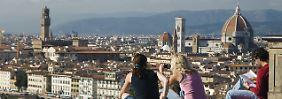 Junge Leute schauen von der Piazzale Michelangelo auf Florenz.