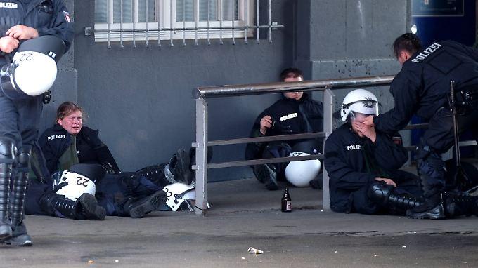 Völlig erschöpfte Polizisten sitzen nach einem Einsatz nahe der Hamburger Landungsbrücken zusammen.