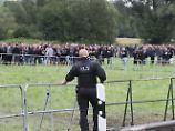Unter den Augen der Polizei warten Konzertbesucher in Themar auf den Einlass zum Konzertgelände.