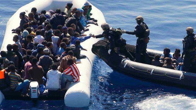 Deutsche Soldaten nehmen afrikanische Flüchtlinge im Mittelmeer auf.