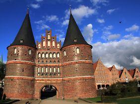 Am Holstentor starten die meisten Reisegruppen ihre Tour durch Lübeck. Daneben stehen alte Salzspeicher.