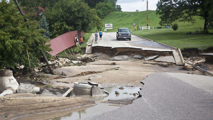 Die Münchener Rück musste im zweiten Quartal für weniger Schäden aufkommen als im Jahr davor. Hier inspizieren Anwohner eine zerstörte Straße nach Gewitterstürmen in den USA.