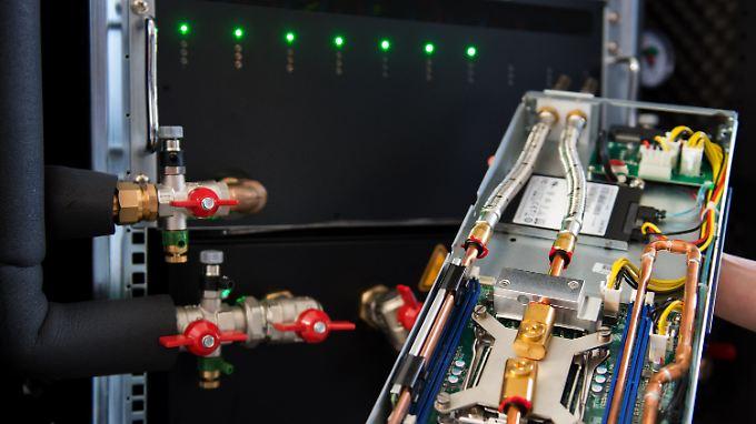 Eine Mitarbeiterin der Cloud & Heat Technologies GmbH, Nicolas Röhrs, hält ein durch Wasser gekühltes Servermodul vor einem Server in den Händen.