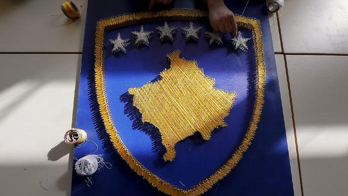Schüler basteln die Flagge des Kosovos.