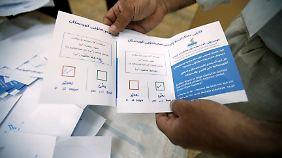 Ein Offizieller präsentiert einen Wahlzettel.