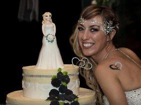 Auf der riesigen Hochzeitstorte steht nur die Braut.
