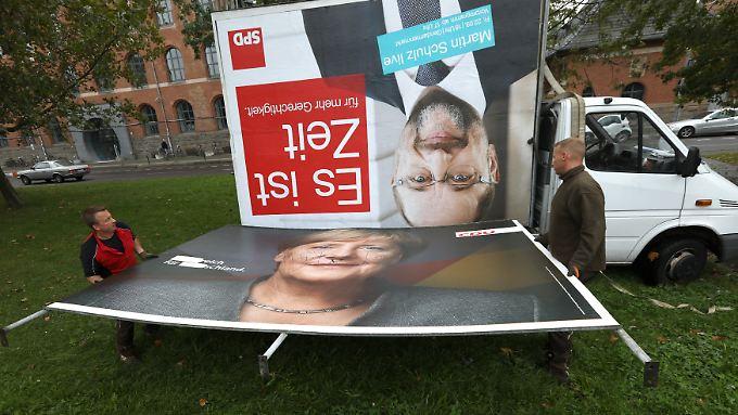 Jetzt wird aufgeräumt: Arbeiter beseitigen in Berlin Wahlplakate mit den Konterfeis von Schulz und Merkel.