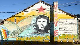 """""""Er lebt"""". Ein Porträt von Che Guevara ziert eine Hausfassade des Krankenhauses Señor de Malta in Vallegrande."""