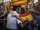 Eine Frau umarmt in Barcelona einen Polizisten der Guardia Civil.