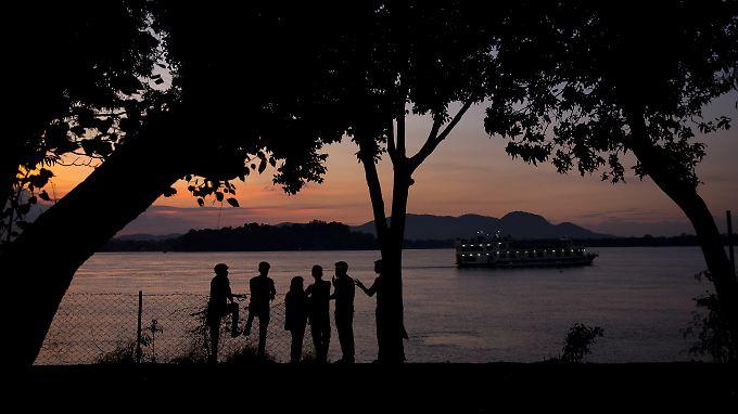 Eine Gruppe beobachtet am Ufer des Brahmaputra im indischen Gauhati den Sonnenuntergang.