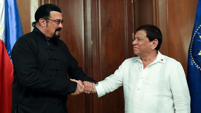 Wäre es ein Film, würde der Held (l.) beim Schurken (r.) eben noch den Puls fühlen - und ihn dann gekonnt überwältigen. So ist es nur ein freundschaftlicher Handshale zwischen Seagal (l.) und Duterte - beide karateerprobt.