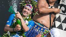 Patrick Lange kann es kaum glauben: Er gewinnt den Ironman auf Hawaii. Die Sektdusche hat er sich verdient.