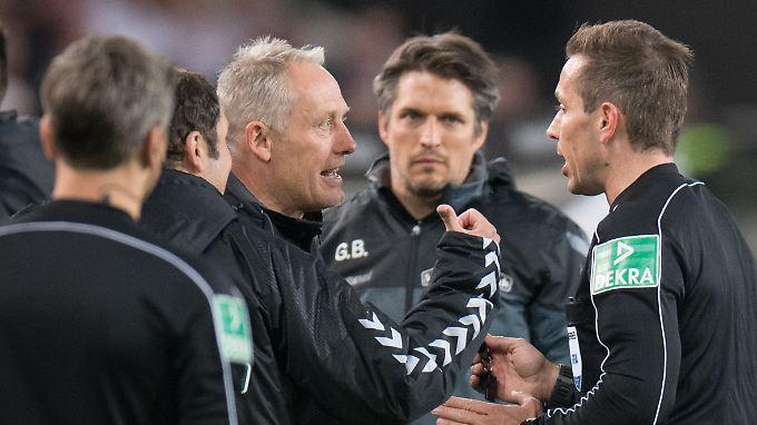 Freiburgs Trainer Christian Streich (l.) diskutiert mit Schiedsrichter Tobias Stieler (r.) - ohne Erfolg.