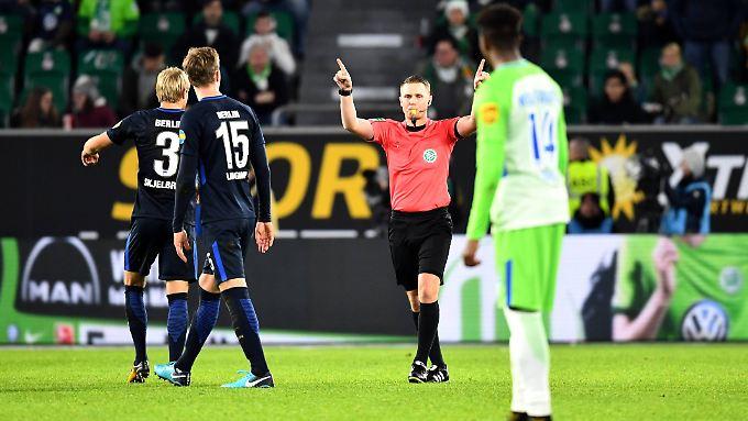 Schiedsrichter Robert Kampka wird beim Spiel zwischen Wolfsburg und Hertha zweimal vom Videoschiedsrichter korrigiert - beide Male zu Recht.