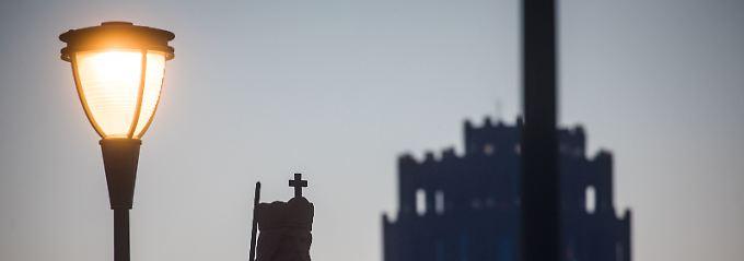 Frankfurt am Morgen: Die Statue von Karl dem Großen auf der Alten Brücke neben der Silhouette des 88 Meter hohen Main Plaza (r).