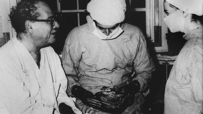 Der südafrikanische Chirurg Christiaan Barnard (M) mit seinem zweiten Herztransplantations-Patienten Philip Blaiberg (l). Rechts eine Krankenschwester. In seinen Händen hält Barnard einen Beutel mit dem kranken Herzen, das er Blaiberg entnommen hatte.