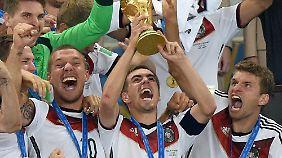 Philipp Lahm reckt 2014 den WM-Pokal in die Höhe.
