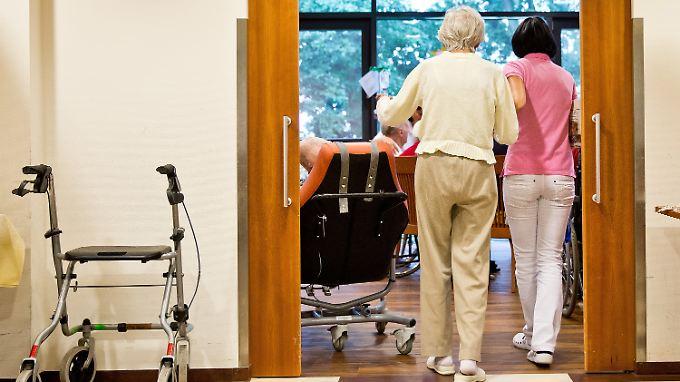 Eine auf Demenzkranke spezialisierte Pflegerin begleitet eine ältere Frau.