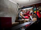 DHL-Mitarbeiter entladen in einer mechanisierten Zustellbasis in Frechen (Nordrhein-Westfalen) einen Lkw.