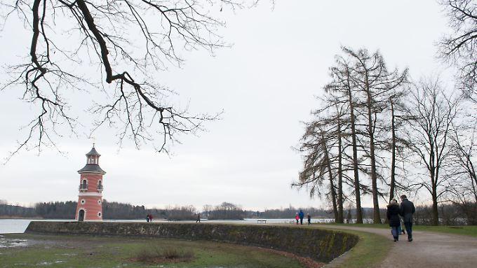 Grauer Himmel: Spaziergänger am 27. Dezember in Moritzburg (Sachsen) vor dem Leuchtturm am Ufer des Großteichs.