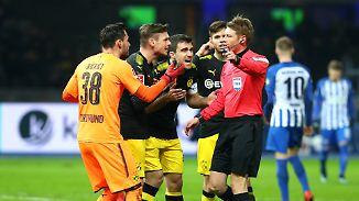 Jetzt schauem Sie doch noch mal nach: Dortmunds Borussen bedrängen Schiedsrichter Christian Dingert.