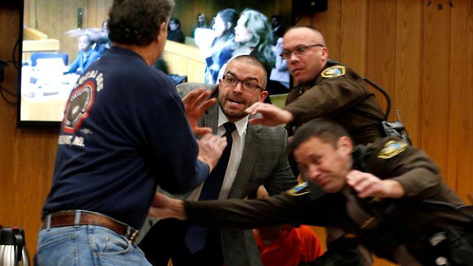 Der Vater (l.) versucht, Nassar (im Hintergrund in oranger Kleidung) zu erreichen.
