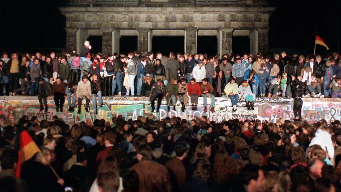 Jubelnde Menschen stehen am 10. November auf der Mauer am Brandenburger Tor - am Tag zuvor war die Grenzbefestigung gefallen.