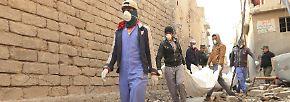 Um Krankheiten zu verhindern, bergen städtische Angestellte und die wenigen Bewohner Mossuls ...
