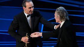 Christopher Walken überreicht Alexandre Desplat den Oscar für seine Musik.