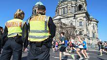 Polizisten stehen am Rande des Halbmarathons in Berlin.