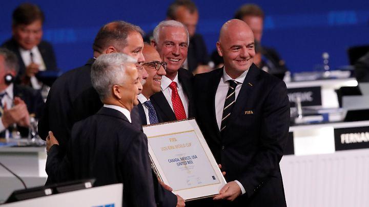 Fifa-Präsident Gianni Infantino (r) posiert nach der Erklärung, dass die WM 2026 in den USA, Mexiko und Kanada stattfinden wird.