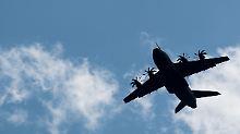 Ein Transportflugzeug der Luftwaffe fliegt am Tag der Bundeswehr über die Menge der Schaulustigen.