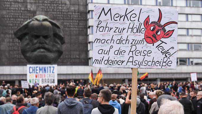 """Das Plakat der Initiative #wirsindmehr hängt noch. Jetzt stehen allerdings Anhänger von """"Pro Chemnitz"""" vor der Karl-Marx-Büste, dem sogenannten Nischel."""